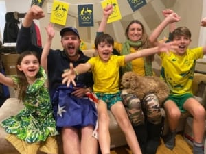 A family dressed in green and gold celebrating the Tokyo Olympic Games